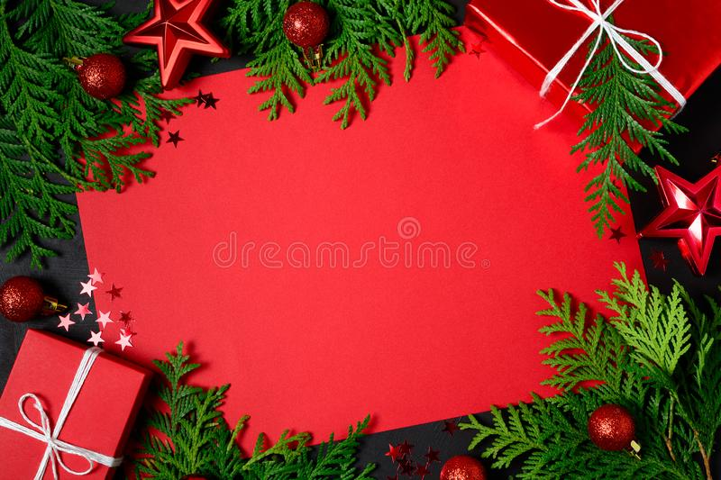 Christmas frame of red gift boxes, fir branches, confetti, paper for text and toys on black background. Flat lay. Top view. Copy royalty free stock images