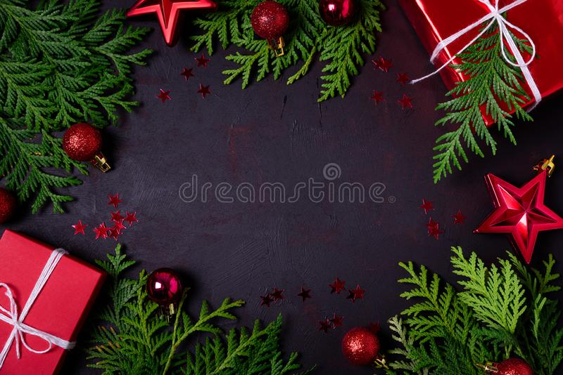 Christmas frame of red gift boxes, fir branches, confetti and toys on black background. Flat lay. Top view. Copy space royalty free stock photography