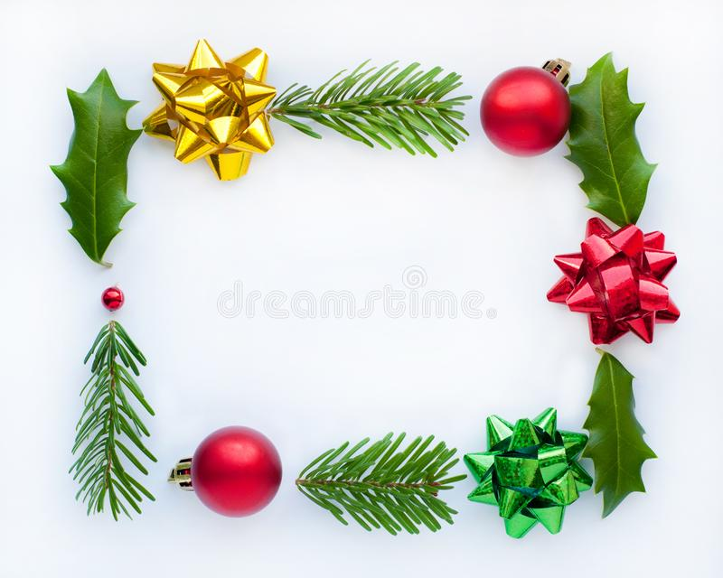 Christmas frame. Red, yellow, green bows on a white background. Leaves of Holly and fir branches. Christmas balls stock images