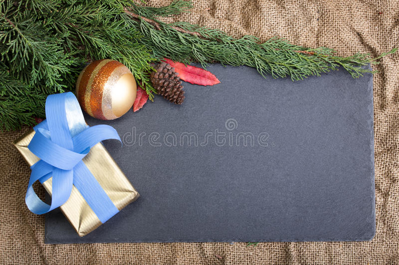 Christmas frame rustic with needles fir tree, xmas balls, gift a. Christmas frame nature with balls, pineapples, fir and the center board for copyspace / royalty free stock image