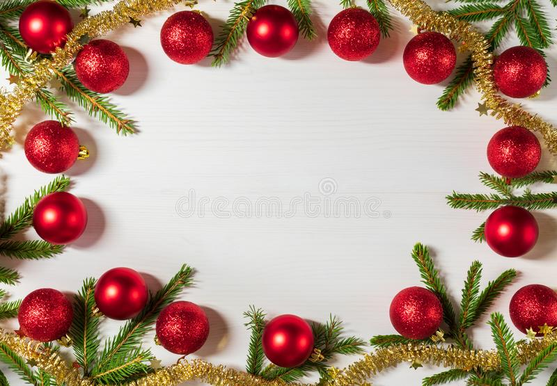 Christmas frame of spruce branches, red balls and gold tinsel. Christmas background on the white wooden desk. Flat lay royalty free stock photos