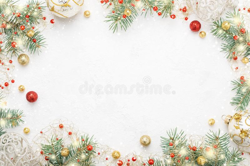 Christmas frame of spruce, red & gold christmas decorations on w. Hite background. Copy space. New Year lights. Flat lay stock photography