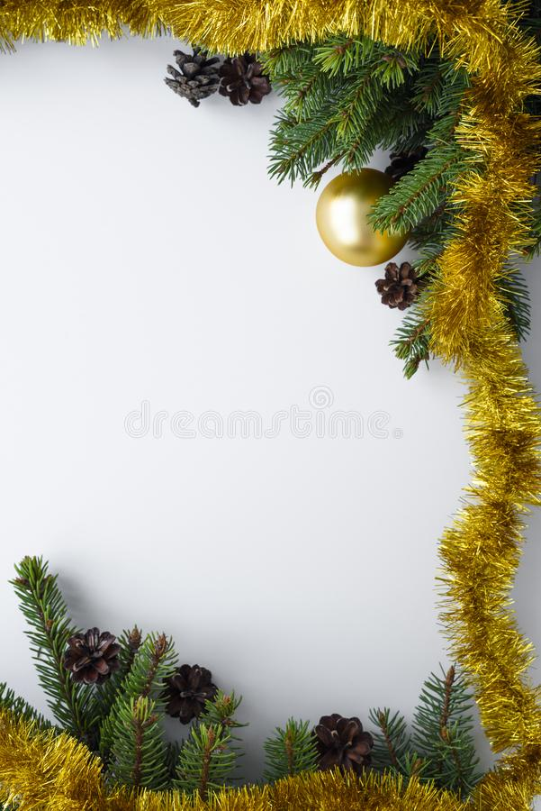 Christmas frame vertical, with festive decorations such as gold tinsel, baubles, conifer tree branches and cones. Copy space for. Christmas frame in vertical royalty free stock photo