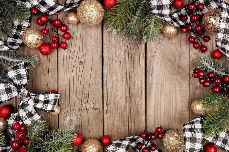 christmas frame white black checked buffalo plaid ribbon baubles tree branches top view rustic wood background 163888219