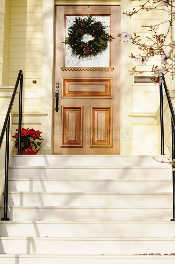 Christmas Front Porch. Front porch with windowed door and wreath, pointsettia and tree branches at the top of stairs royalty free stock images