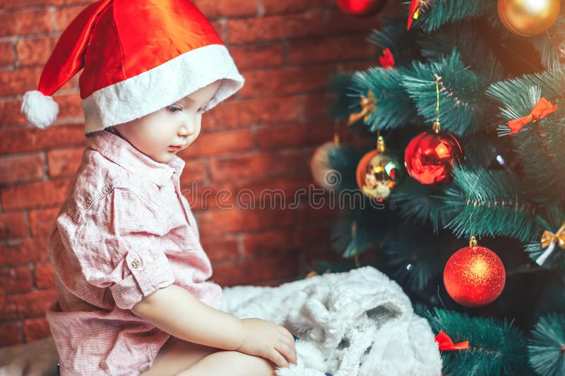 Happy Little baby in Santa`s hat sit near Christmas tree in the holiday night. New Year`s holidays and Christmas tree. royalty free stock photo