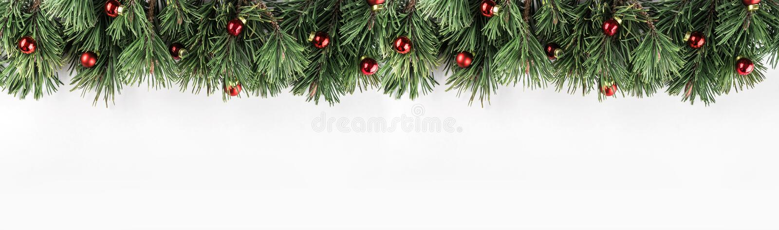 Christmas garland of Fir branches with red decoration on white background. Xmas and Happy New Year theme. Flat lay, top view, wide composition royalty free stock images