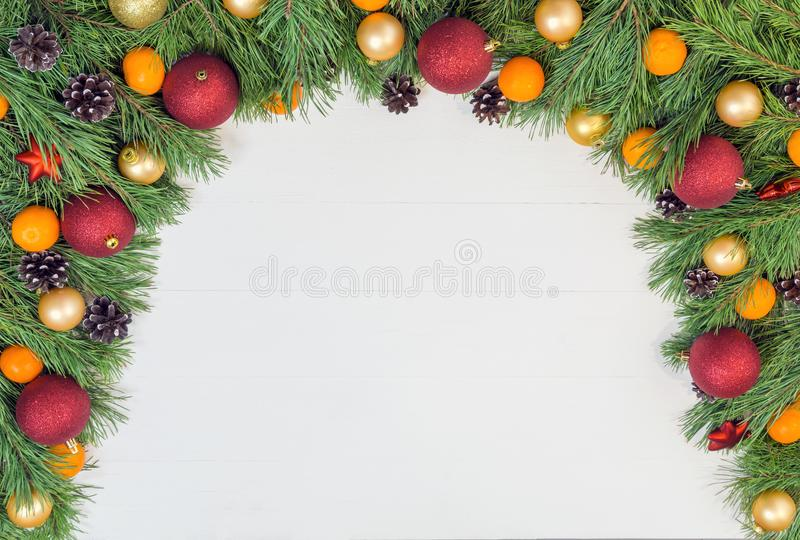 Christmas garland with green natural pine branches with cones on white wooden background stock photo