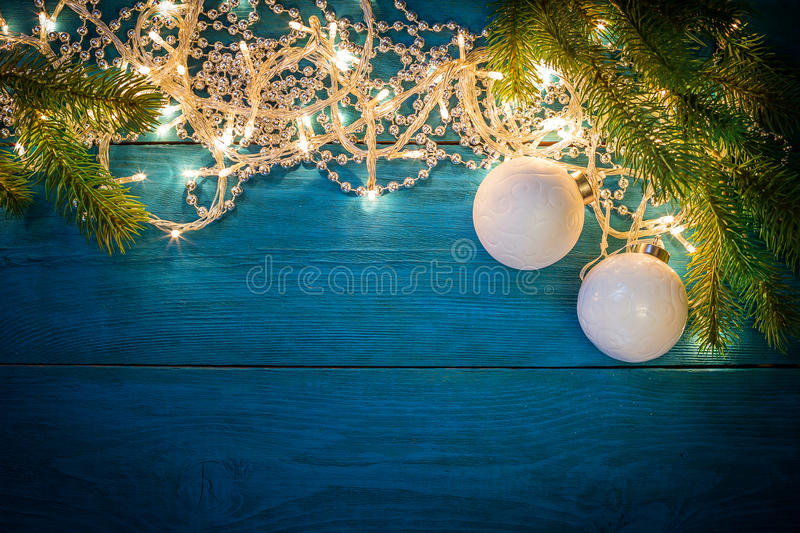Christmas garland lights. Glowing Christmas lights, silver beads and a white Christmas balls on a blue wooden background. Top view with copy space royalty free stock image