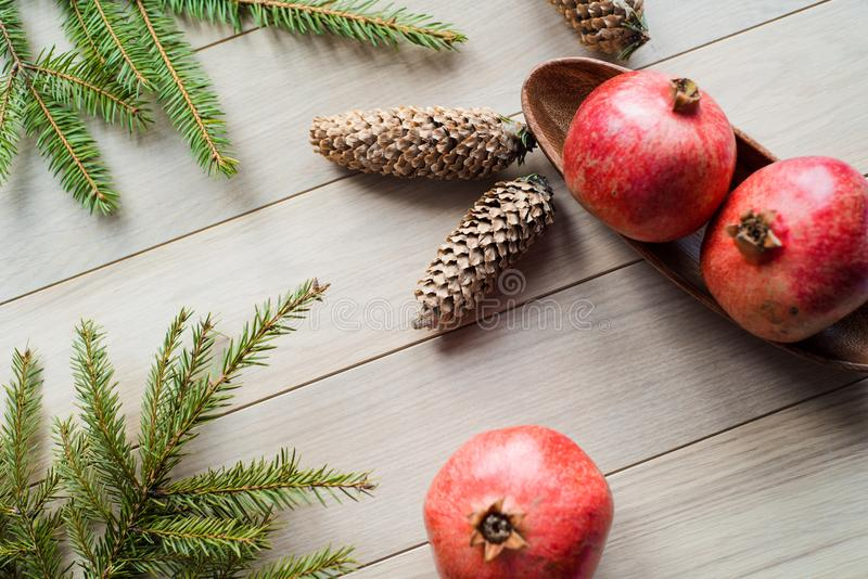 Christmas garnet fruit, spruce tree branch, big bumps on a textured background royalty free stock photo