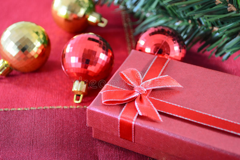 Christmas gift. Red Christmas gift box and Cristmas balls on red fabric background
