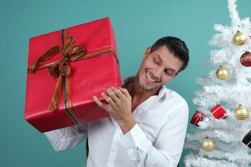 Christmas gift. Happy man with christmas gift present with white christmas decorative royalty free stock image