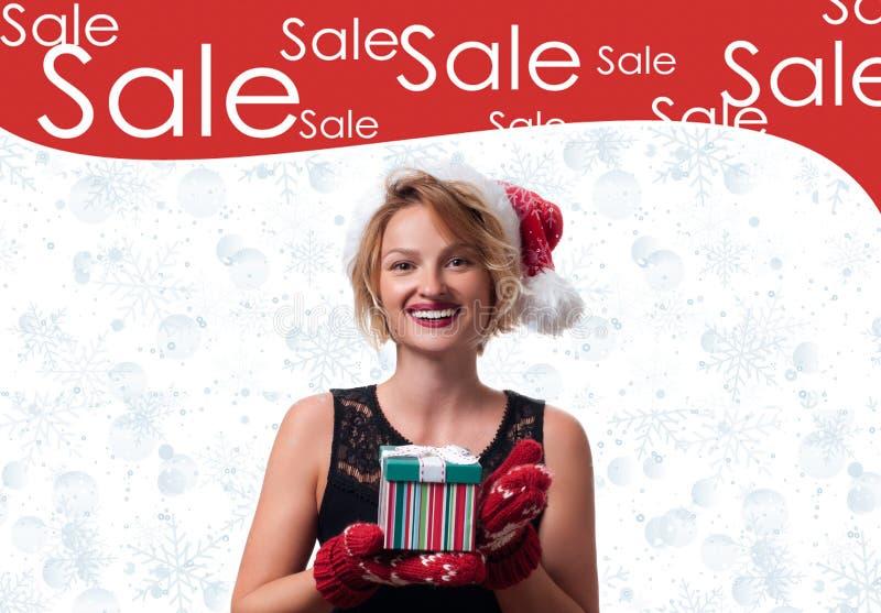 Christmas gift. Beautiful womanin santa hat. Holiday sale stock photography