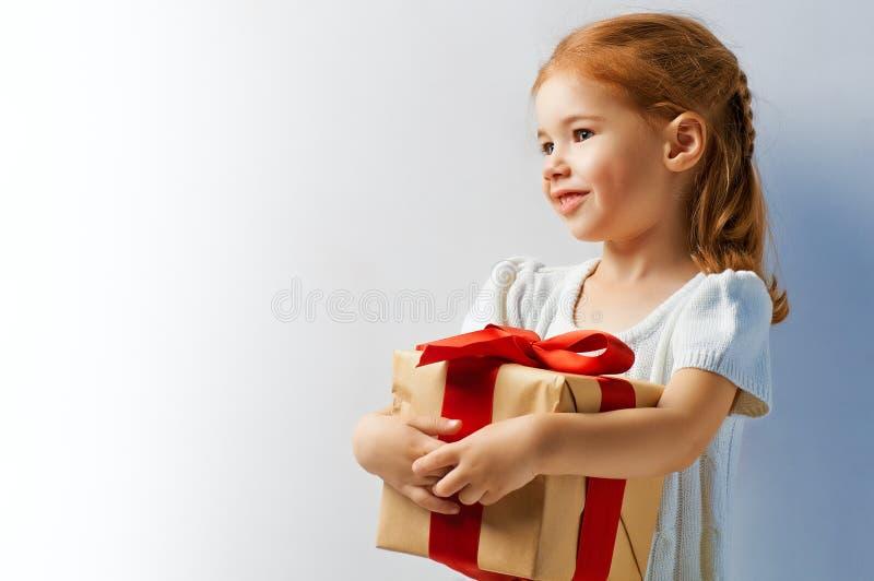 Christmas gift. Beauty childl with christmas gift stock photo
