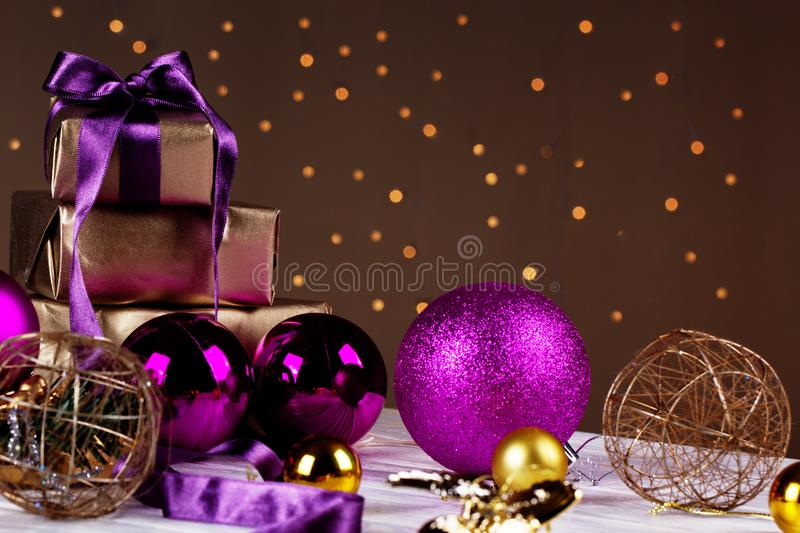 Christmas gift box and baubles on background of defocused golden stock image