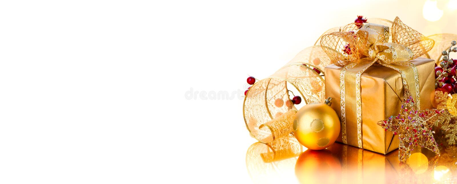 Christmas Gift box with baubles. Beautiful New Year decorated golden gift, border design, isolated on white background royalty free stock image