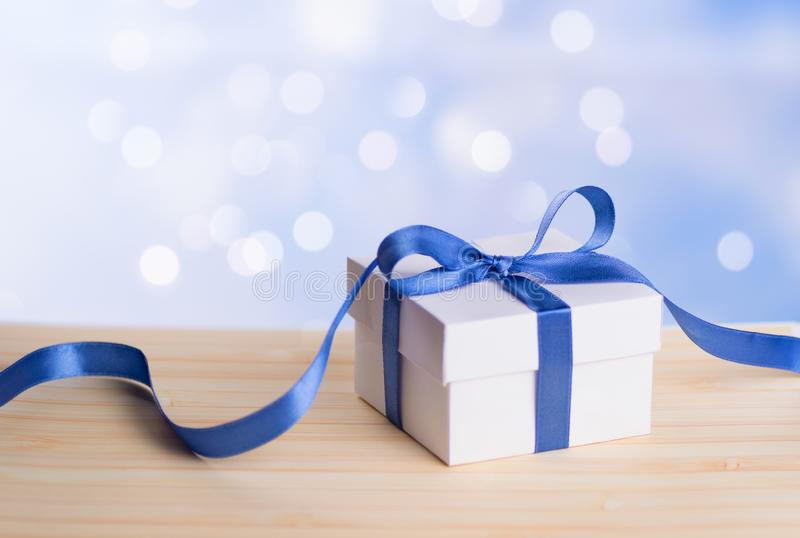 One Christmas gift box with blue ribbon bow and bokeh background. royalty free stock photos