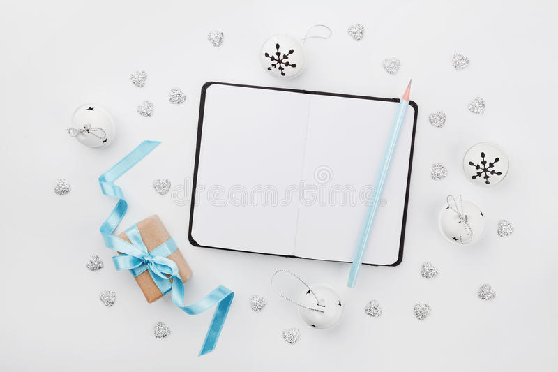 Christmas gift box with blue ribbon, empty notebook and jingle bell on white desk above. Holiday greeting card. Mockup. Flat lay. Christmas gift box with blue stock images