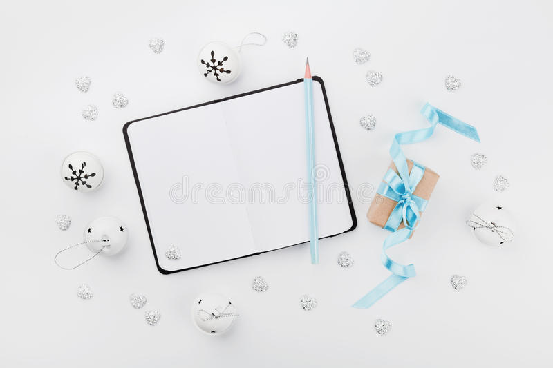 Christmas gift box with blue ribbon, empty notebook and jingle bell on white table above. Holiday greeting card. Mockup. Flat lay. Christmas gift box with blue stock images