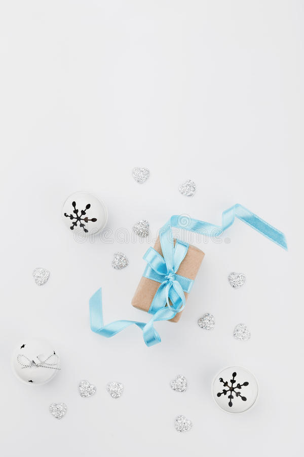 Christmas gift box with blue ribbon and jingle bell on white background from above. Holiday greeting card. Mockup. Flat lay royalty free stock photos
