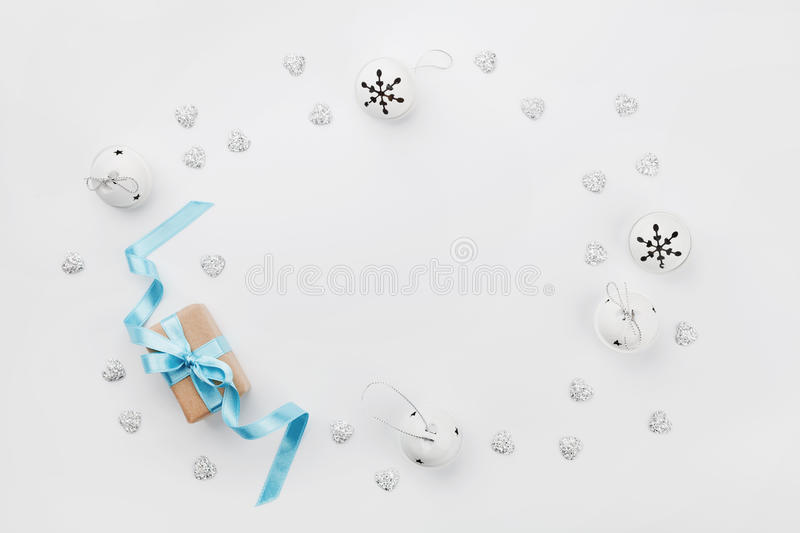 Christmas gift box with blue ribbon and jingle bell on white table from above. Holiday greeting card. Mockup. Flat lay frame. stock photography