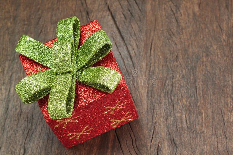 Christmas gift box with a bow on a wooden texture. royalty free stock photography