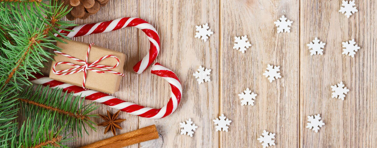 Christmas gift box, candy cane with snowflake and fir tree branch on wooden table royalty free stock photography