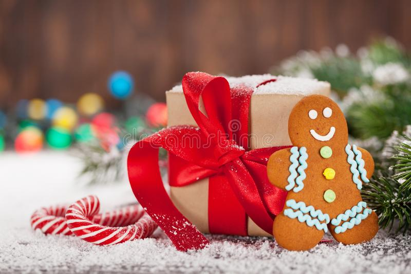 Christmas gift box, candy canes and gingerbread man. Christmas gift box, candy canes, gingerbread man and snow fir tree. Xmas greeting card stock images
