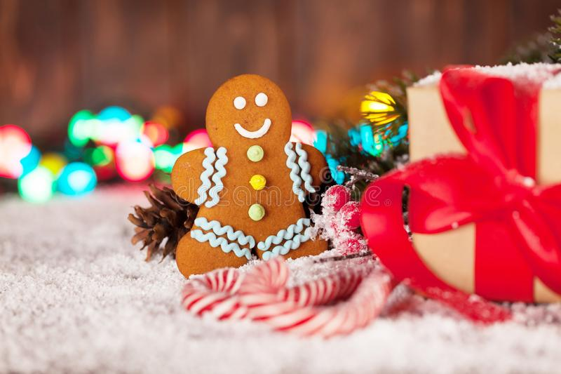 Christmas gift box, candy canes and gingerbread man. Christmas gift box, candy canes, gingerbread man and snow fir tree. Xmas greeting card royalty free stock photos