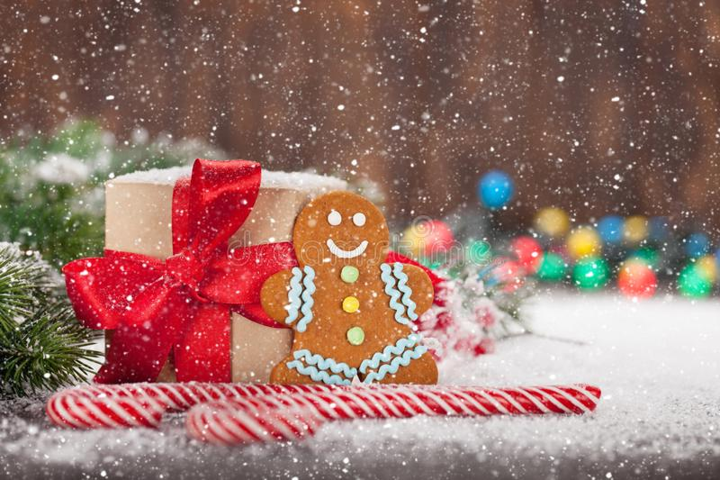 Christmas gift box, candy canes and gingerbread man. Christmas gift box, candy canes, gingerbread man and snow fir tree. Xmas greeting card with copy space stock photo