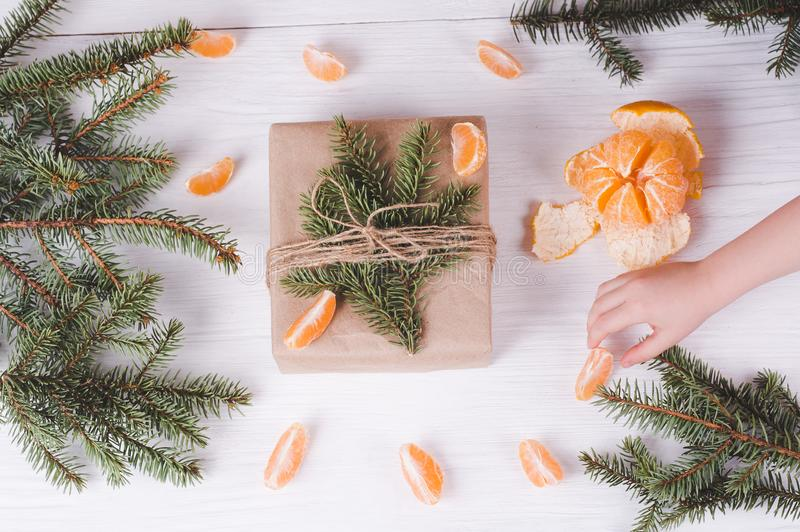 Christmas gift box, child`s hand and tangerines on a white wooden background. Christmas & New Year composition.  royalty free stock photo