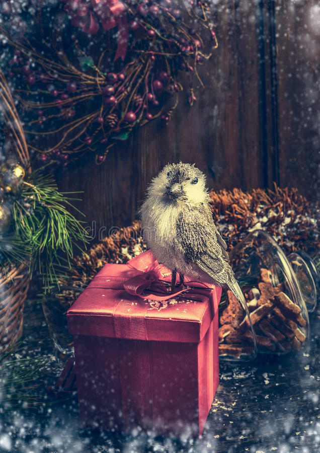 Christmas gift box with decoration bird on rustic table over dark wooden background royalty free stock photography