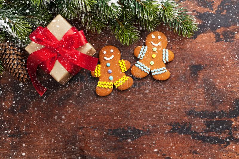 Christmas gift box, gingerbread cookies and fir tree branch covered by snow on wooden background. Top view xmas backdrop with stock photos
