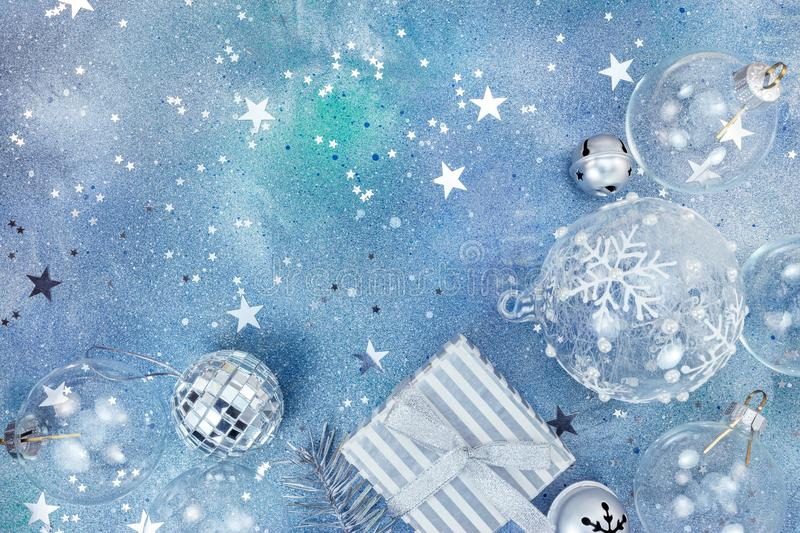 Christmas gift box among glass balls and silver jingle bells on. Starry blue background stock photo