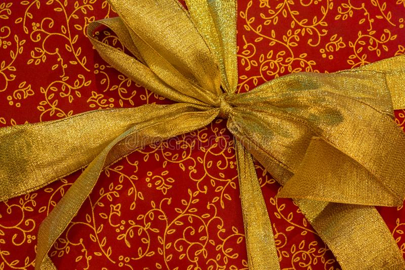 Christmas gift box with a gold ribbon bow on red wrapping paper with gold pattern. Good New Year spirit. royalty free stock photo
