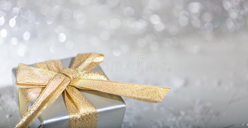 Christmas gift box with golden ribbon on abstract bokeh lights and glitter background royalty free stock photos