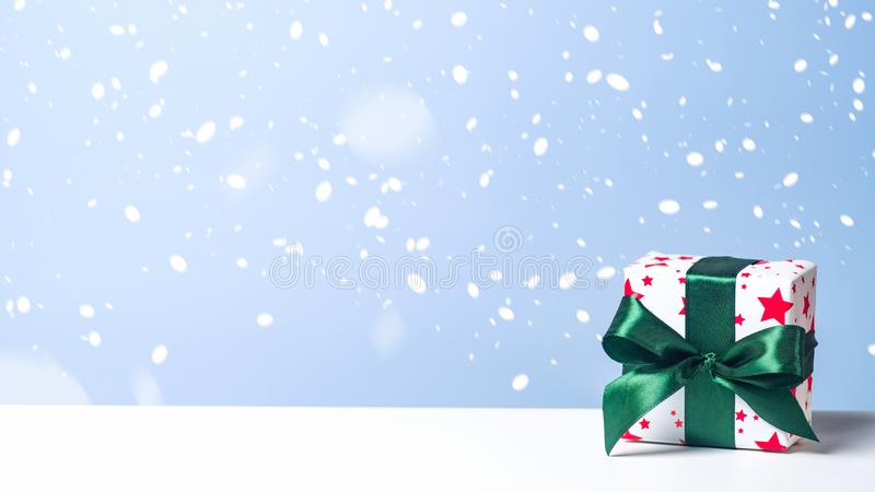 Christmas gift box with green ribbon bow in snow on blue background. Christmas, New Year, winter holidays concept royalty free stock photo