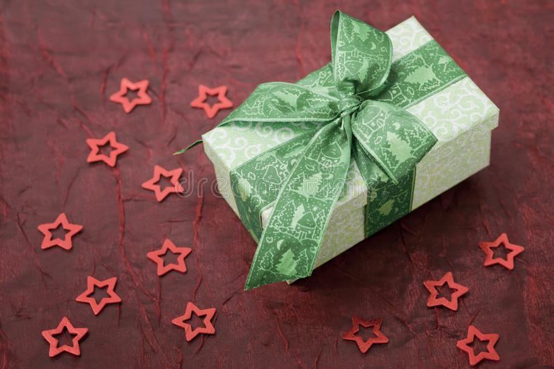 Christmas gift box with green ribbon on a red cloth. stock image