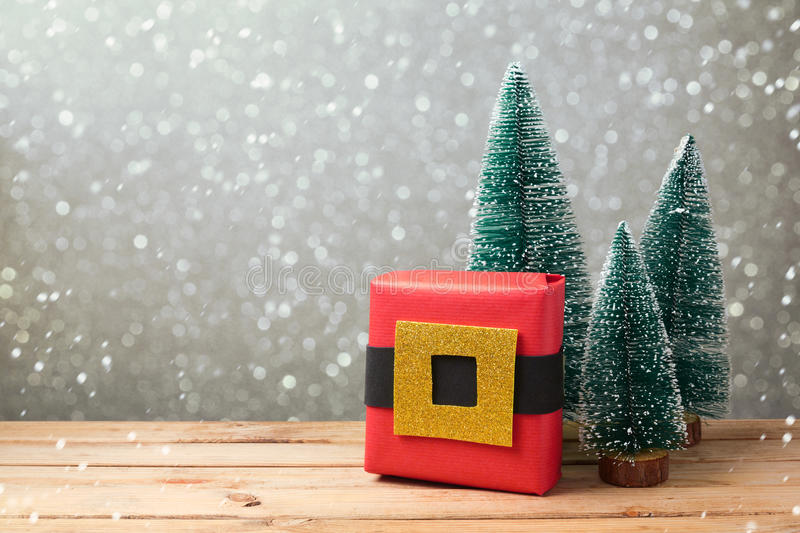 Christmas gift box with homemade creative wrapping on wooden table over bokeh background stock photography