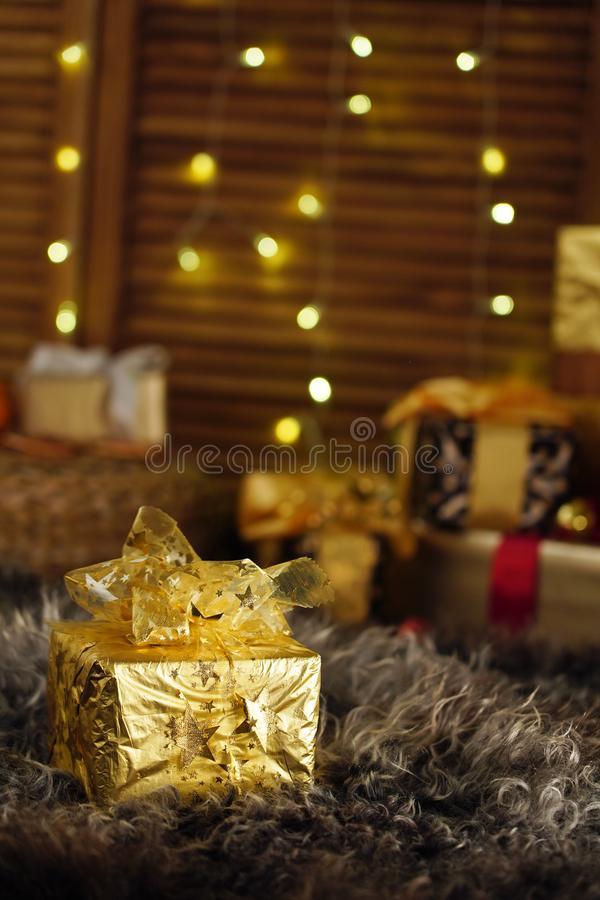 Christmas gift, gift box Packed in gold foil and tied with a ribbon. there are many gifts in the background stock photography