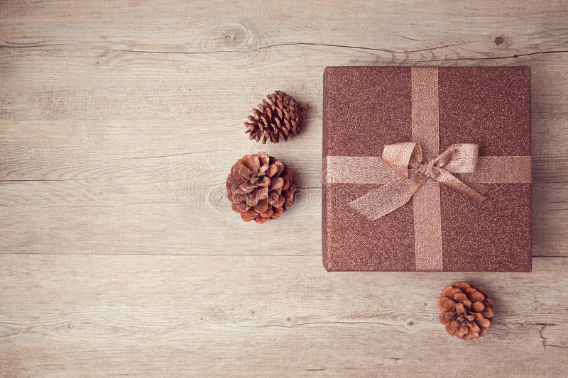 Christmas gift box with pine corn on wooden background. View from above royalty free stock photography