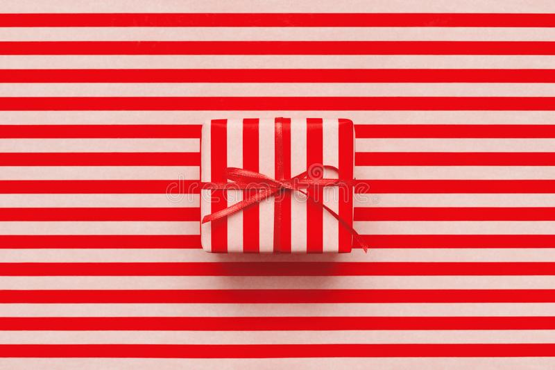 Christmas gift box on pink and red striped wrapping paper. royalty free stock photos