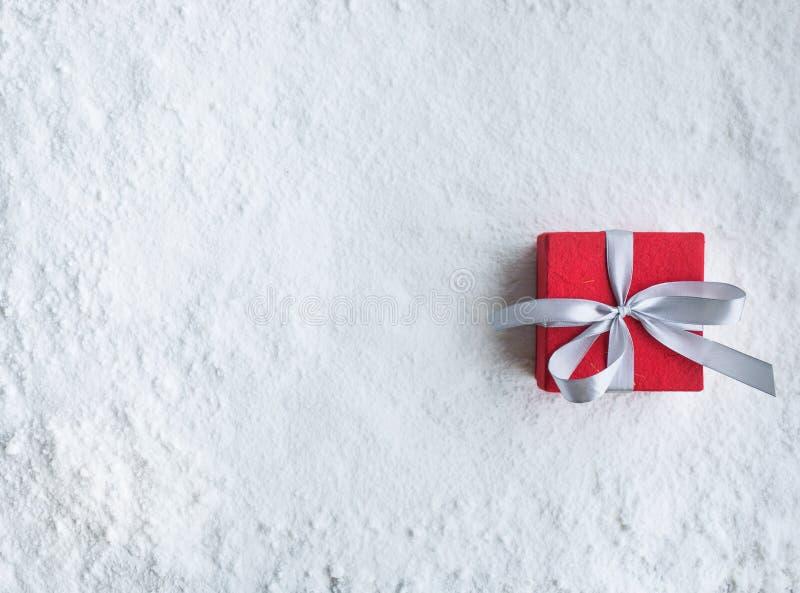 Christmas gift box,present on snow background.For christmas stock photos