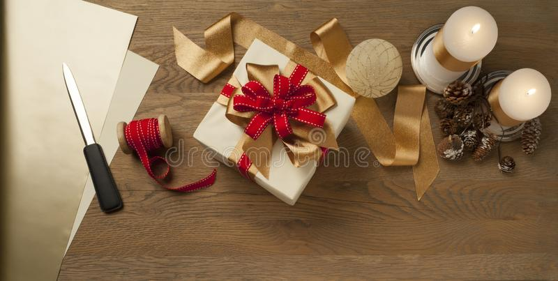 Christmas gift box tied with red and golden bow over a wooden table with candles stock image