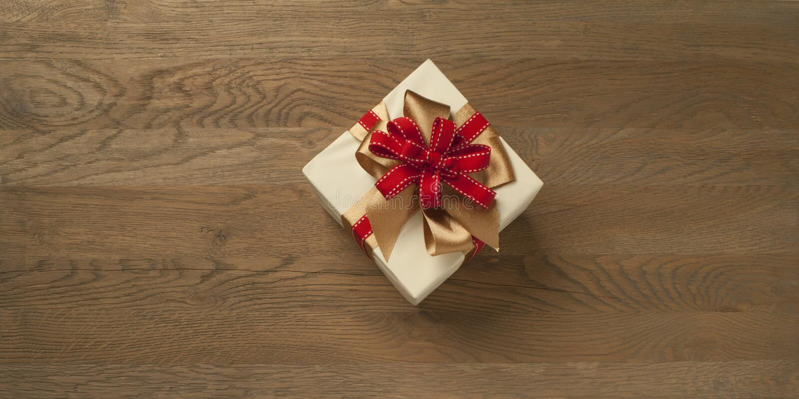 Christmas gift box tied with red and golden bow over a wooden table stock image