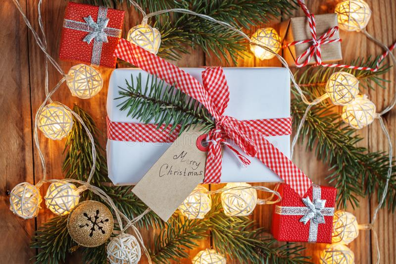 Christmas gift box on wooden background with Fir branches, jingle bell, small presents and Christmas light. Xmas and Happy New Yea royalty free stock image