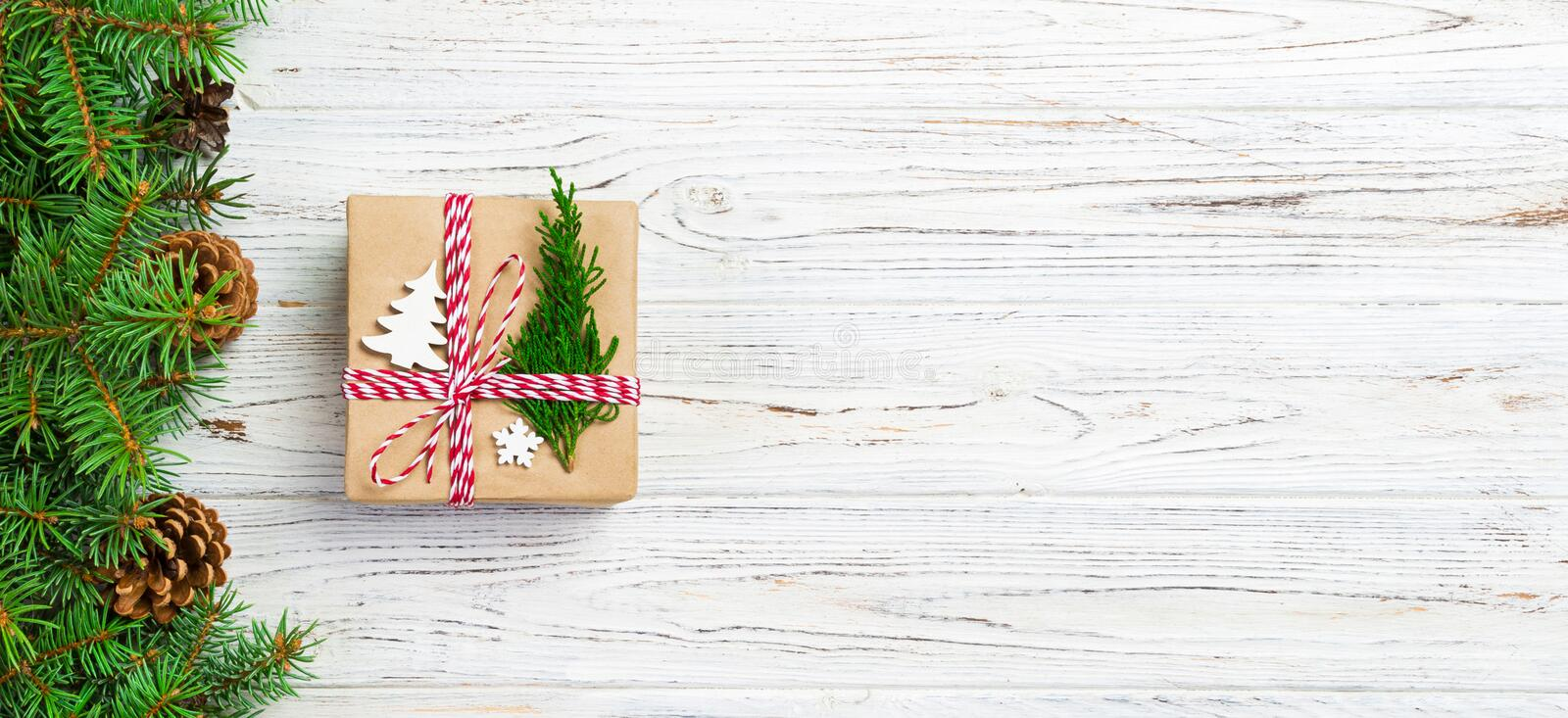 Christmas gift box wrapped in recycled paper, with ribbon bow, with ribbon on rustic background. Holiday banner concept.  stock photos