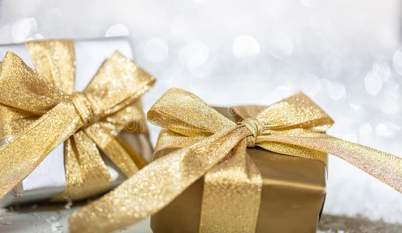 Christmas gift boxes with golden ribbons on abstract bokeh lights and glitter background stock images