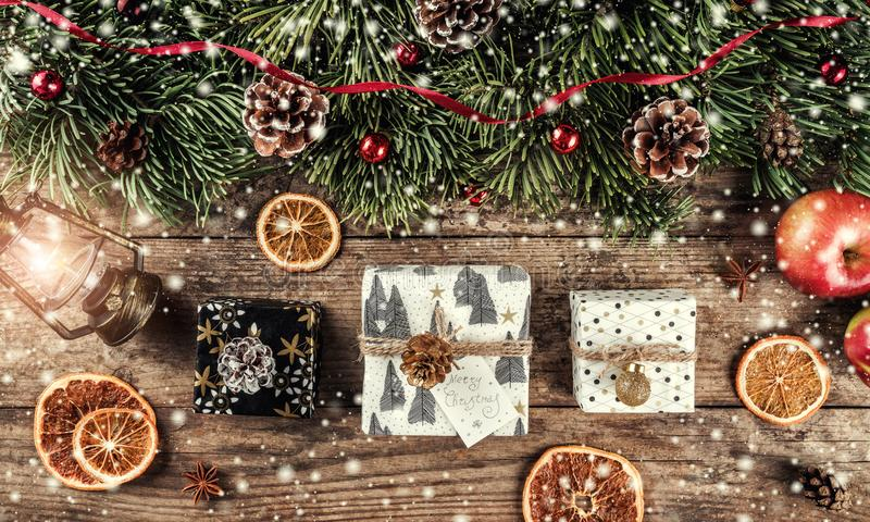 Christmas gift boxes on holiday wooden background with fir branches, lamp, pine cones, red decoration. Xmas and New Year theme,. Bokeh, snow. Flat lay, top view royalty free stock image