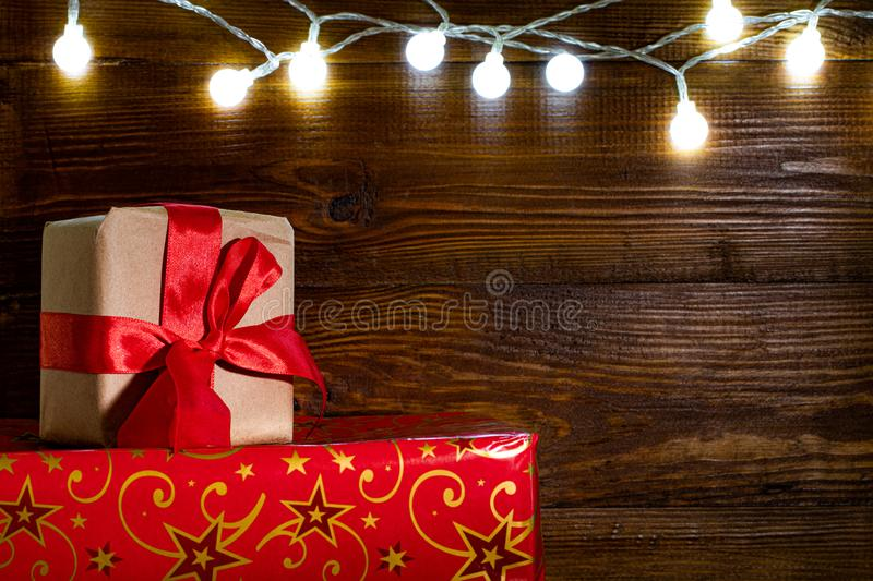 Christmas gift boxes and lights over wooden background, copy space stock image
